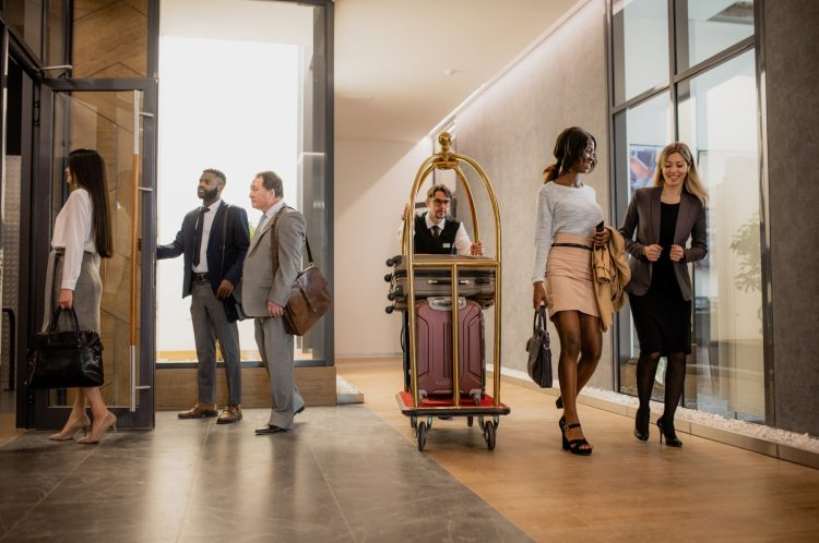 Busy porter pushing cart with baggage while moving among business people interacting on the move in hotel corridor